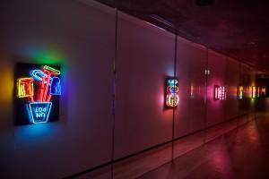 """エントランス横の15mのギャラリースペース。クリエイティブエージェンシー""""ガスアズインターフェイス""""とクリエイティブスタジオ""""YAR""""とのアーティストキュレー ションによる「NEON MUSEUM」が開催中。"""